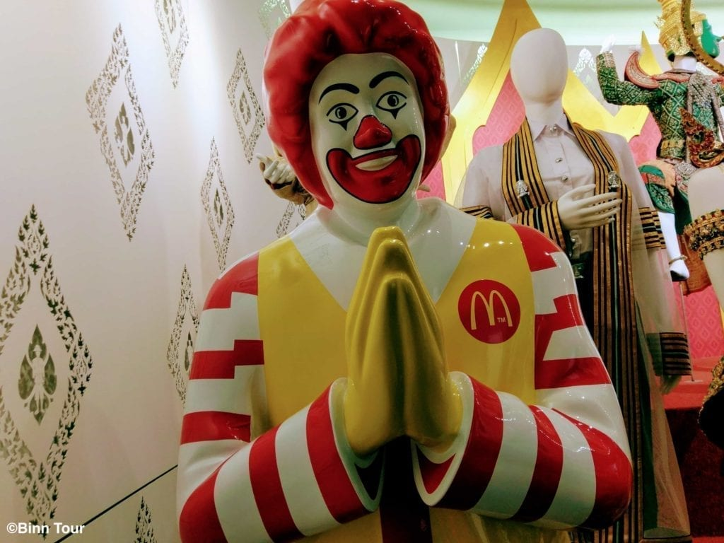 Statue of Ronald McDonald holding his hands in a wai position